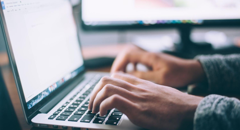 Mand skriver på bærbar computer