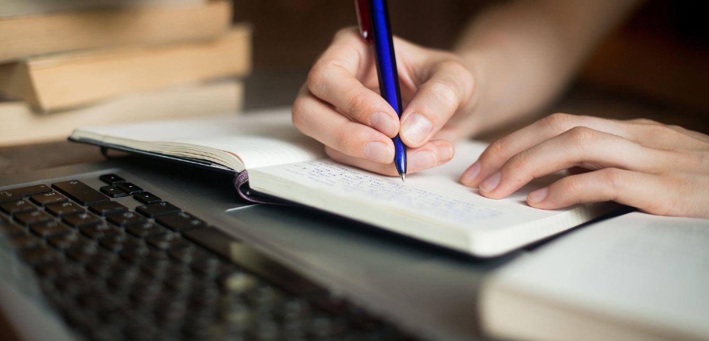 Studerende arbejder med en notesbog og computer