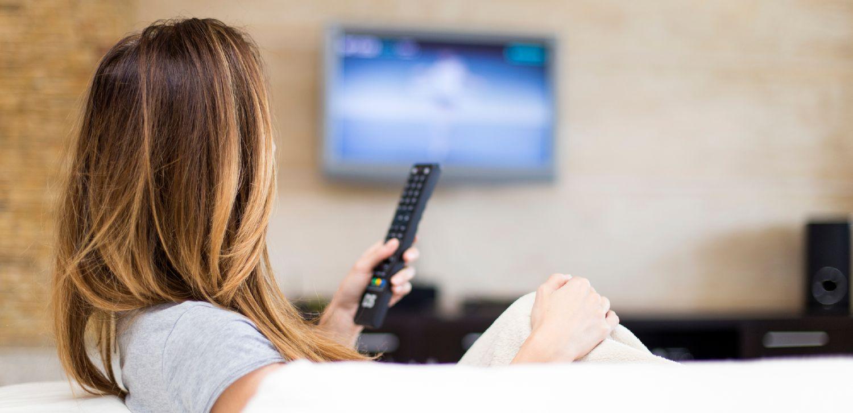 Kvinde sidder i sofa og ser TV