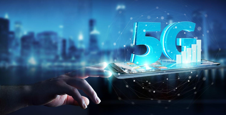 5G ikon på liggende smartphone med blå skyline i baggrunden