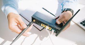 Mand i lyseblå skjorte installerer antenner på ny trådløs router