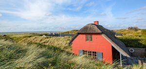 Rødmalet hus med stråtag ved Skagens kyst