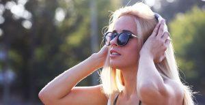 Kvinde med solbriller lytter til musik på sin mobil udendørs