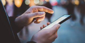 Mand bruger sin mobiltelefon udenfor
