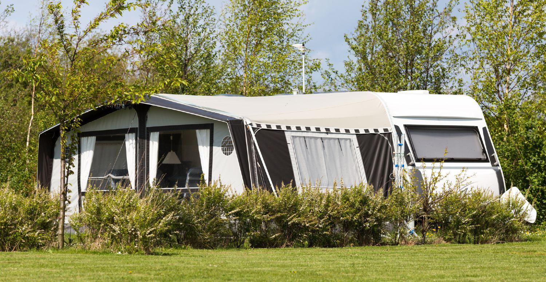 Campingvogn med fortelt på en flot campingplads med solskin