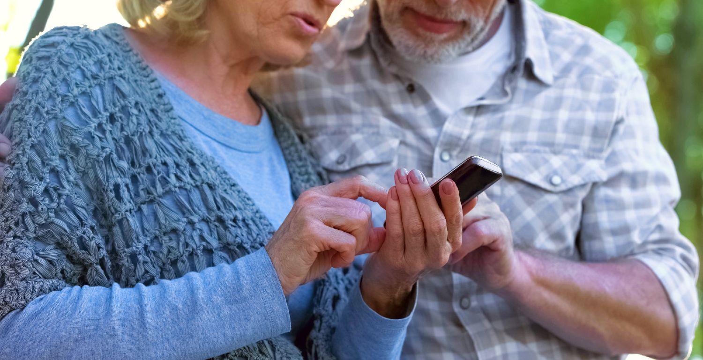 Ældre ægtepar anvender mobiltelefon