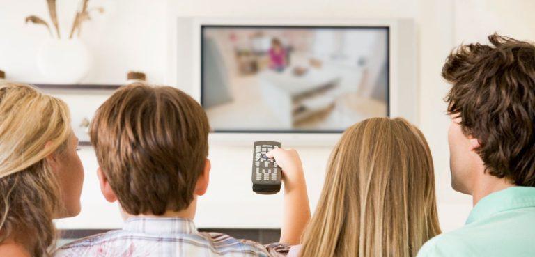 Familie sidder i sofaen og ser TV