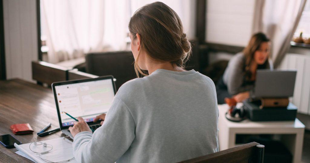 To kvinder arbejder hjemmefra ved spisebordet og sofabordet
