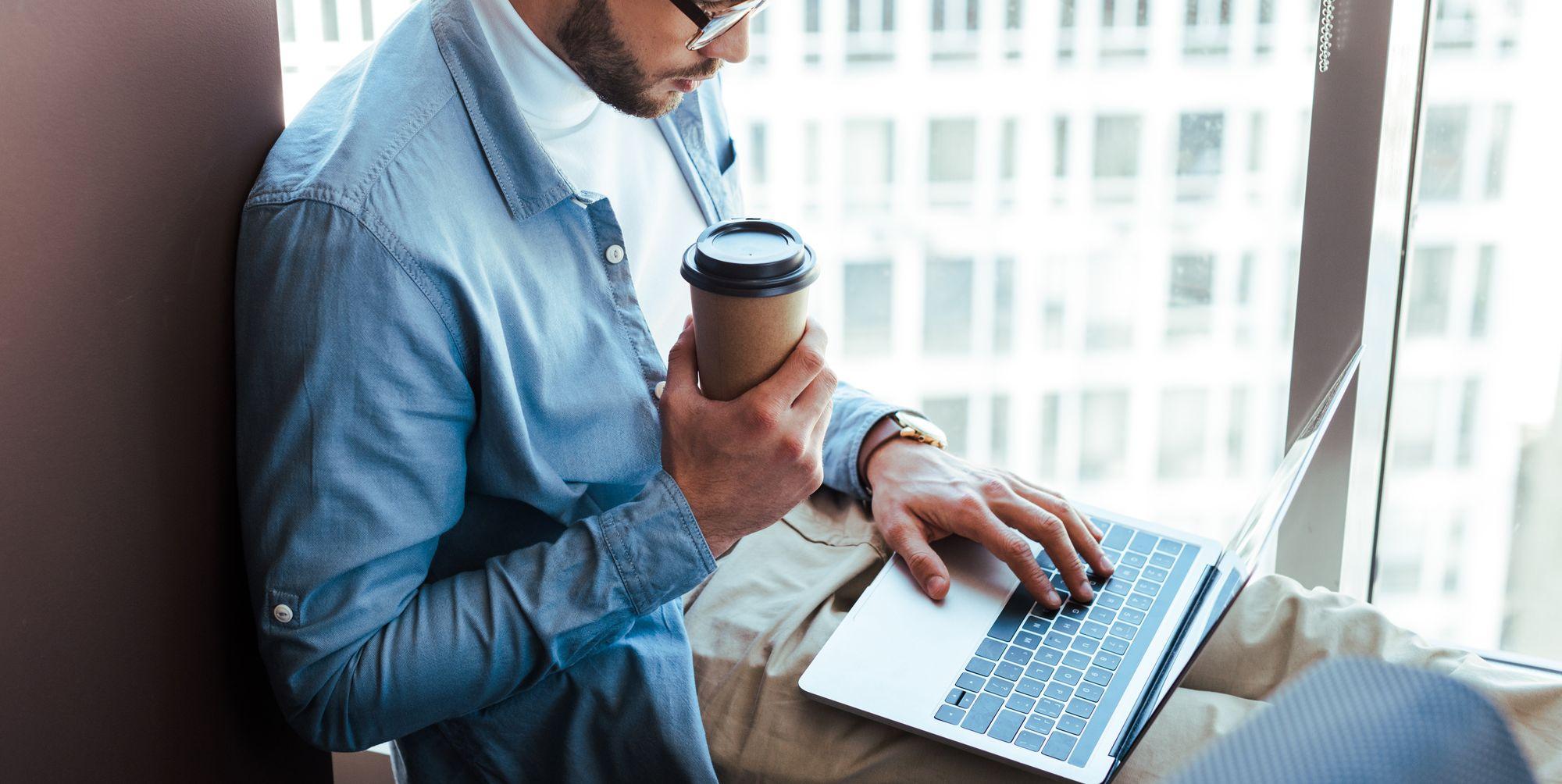 Mand i blå skjorte drikker kaffe og arbejder på bærbar computer