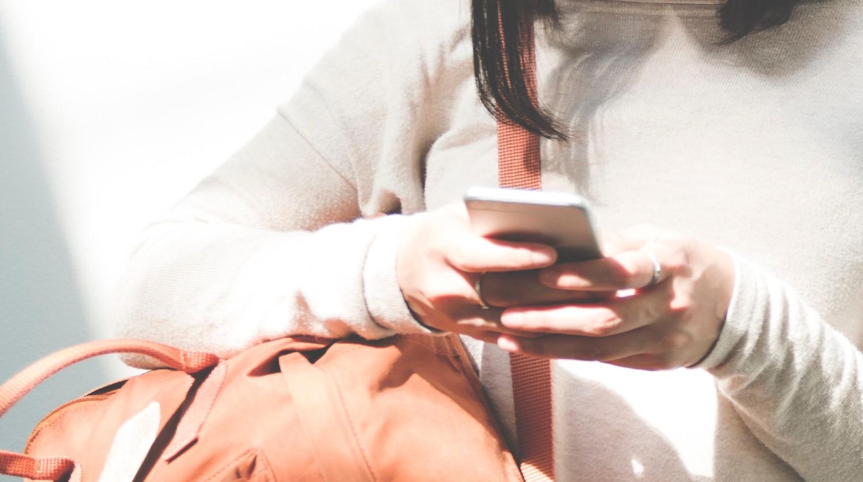 Kvinde med brun lædertaske og hvid bluse anvender iPhone