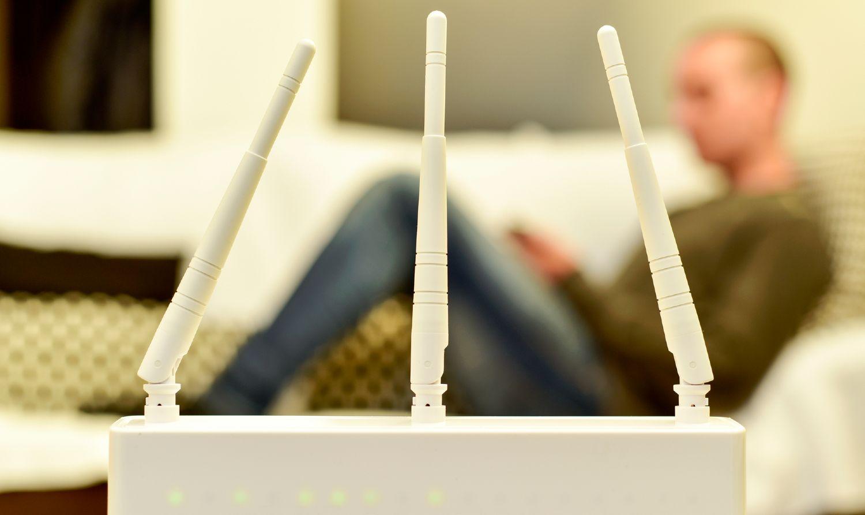 Hvid router med 3 antenner og mand siddende i sofa i baggrunden