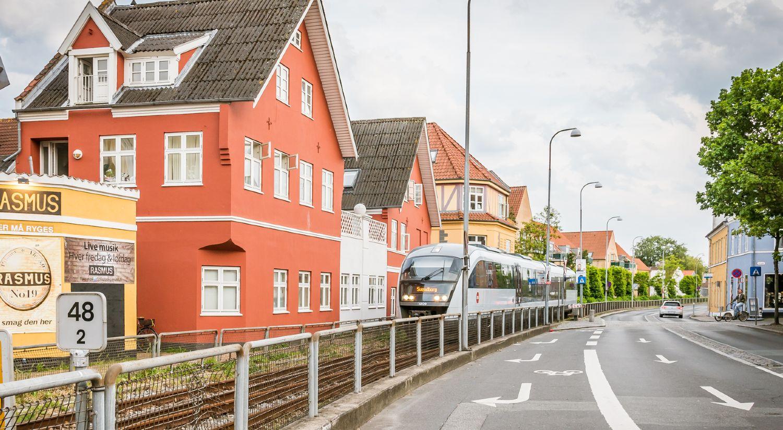 Svendborg by med jernbane og tog på vej til stationen