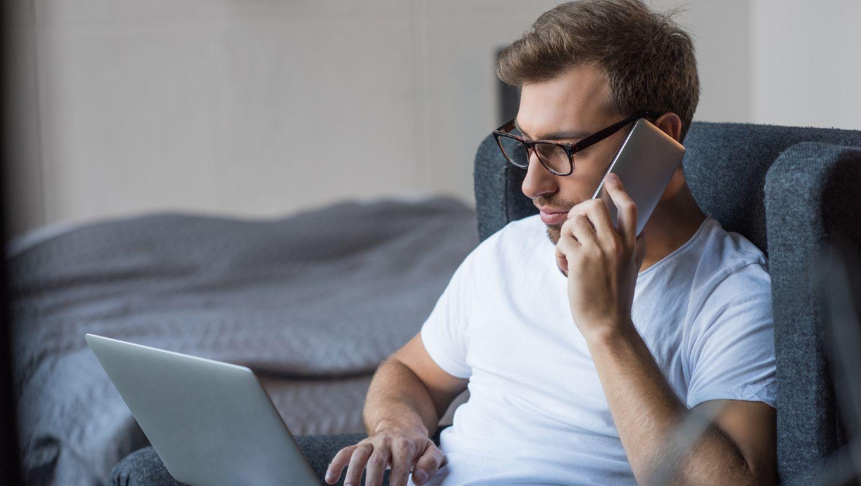 Mand taler i telefon mens han sidder i sin stol med en bærbar computer