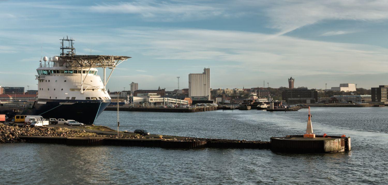 Esbjerg havn med stort skib i vandet og blå himmel