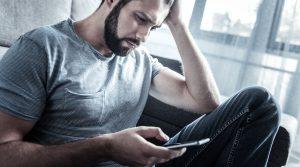 Mand ser på sin telefon og undrer sig over hvem som har ringet til ham