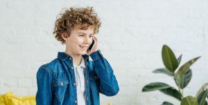 Glad dreng med krøllet hår og cowboyjakke taler i sin mobiltelefon