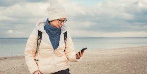 Kvinde på strand tjekker sin mobiltelefon med Storebæltsbroen i baggrunden