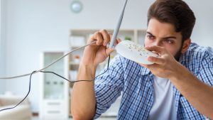 Irritabel mand inspicerer trådløs router