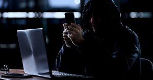 Svindler bruger mobiltelefon og computer i et mørkt lokale