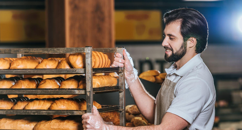 Medarbejder flytter et fyldt stik i en bagerbutik