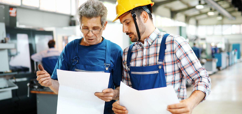 Fabriksarbejdere fører kontrol med produktionsanlæg