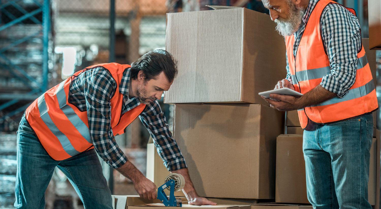 To lagerarbejdere pakker varer i kasser på lager