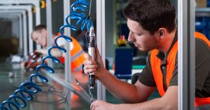 Produktionsarbejder i orange vest på fabrik