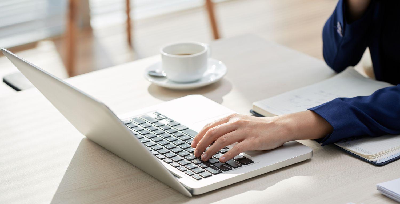 Person med Macbook ved bord med kaffekop