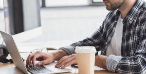 Mandlig udvikler arbejder på bærbar computer med en kop kaffe