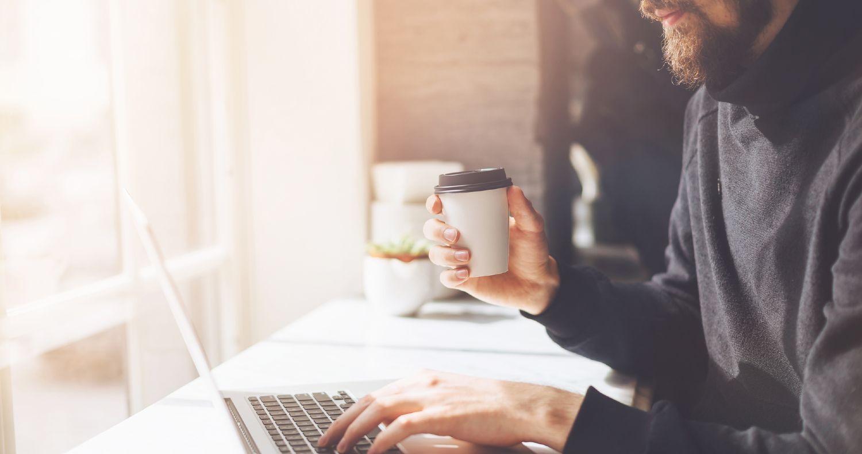 Mand med kaffe i hånden arbejder på bærbar computer ved vindue