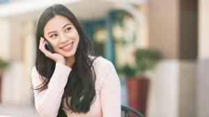 Smilende kvinde snakker i telefon, mens hun sidder ved havebord