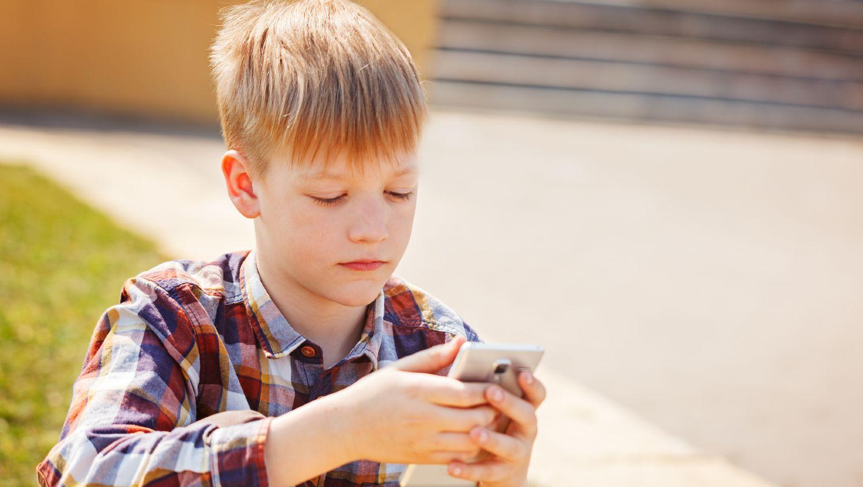 Dreng i ternet skjorte bruger sin mobiltelefon udenfor