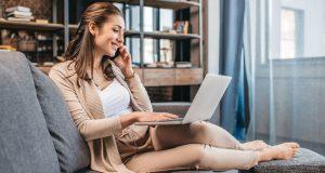 Kvinde med telefon og computer sidder i sofaen i sin stue