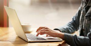 Mand bruger bærbar computer til at surfe på nettet med