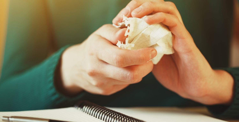 Kvinde i grøn trøje river papir ud af notesblok og krøller det sammen