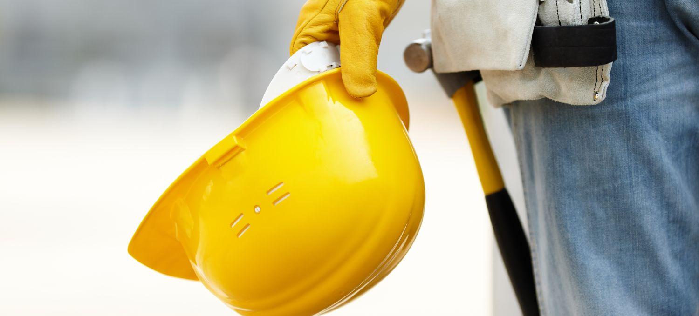 Bygningsarbejder holder gul hat i hånden