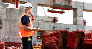 Arbejder i orange refleksvest observerer en byggeplads ved stor betonkonstruktion