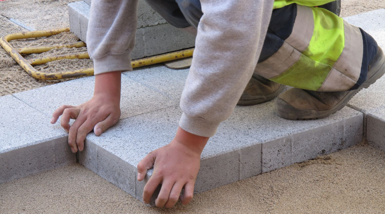 Brolægger i færd med at lægge nye betonfliser