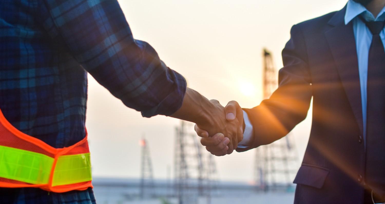 En bygherre og en forretningsmand deler et håndtryk ved en byggeplads
