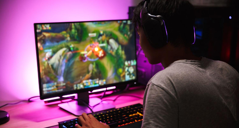 Ung mand spiller computer på nettet