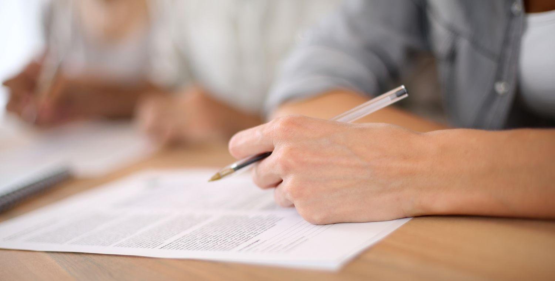 Jobsøgende udfylder en jobansøgning i hånden
