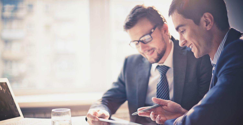 To mænd i jakkesæt afholder samtale på kontor
