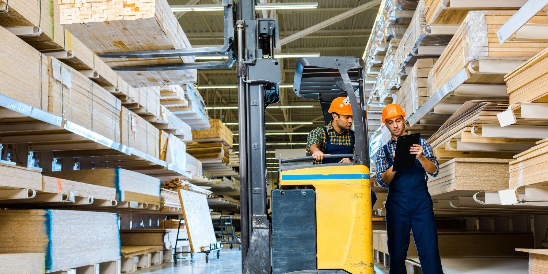 Lagerarbejdere i færd med at hejse trævarer ned med gaffeltruck