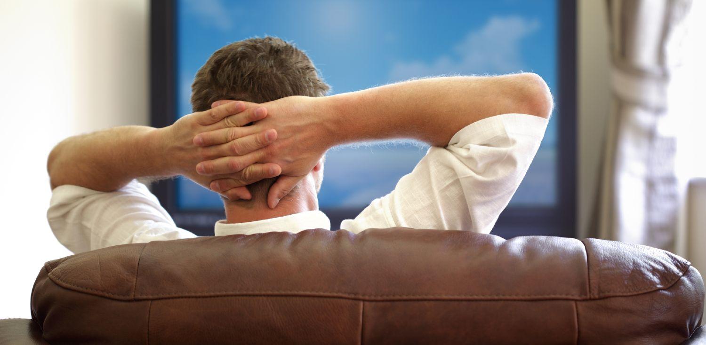 Mand sidder i brun lædersofa og ser TV
