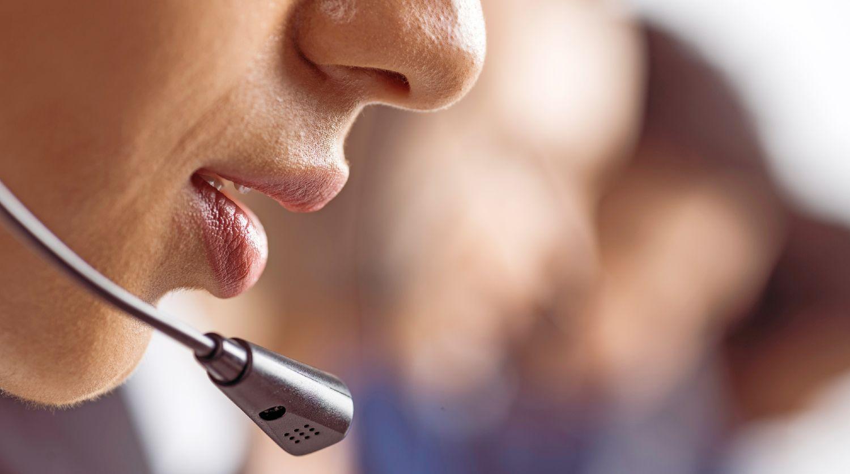 Telefonsælger sidder ved siden af andre sælgere, mens han taler ind i et headset